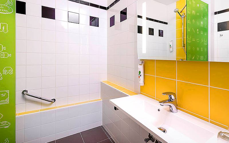 White, green and yellow tiled bathroom, featuring a sink and walk in shower