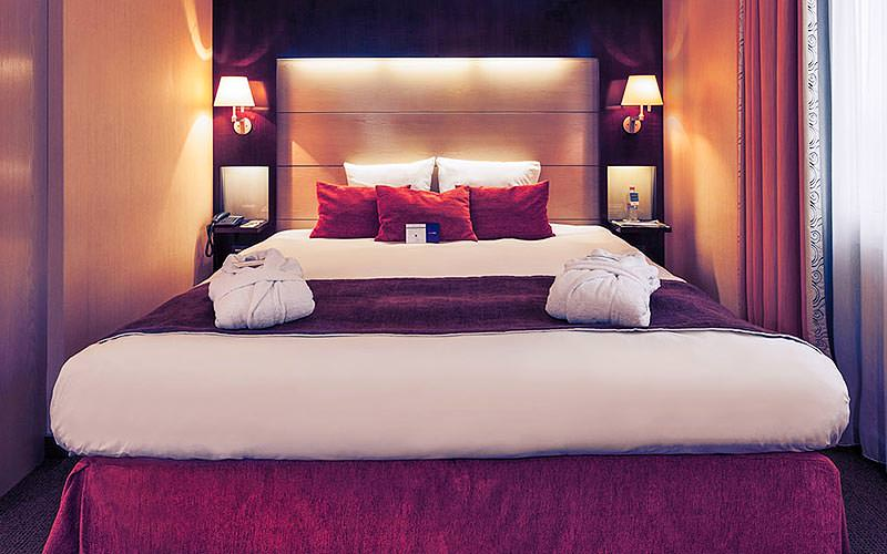A double bed topped with a red throw, cushions and white folded towels, with lit bedside lamps on either side