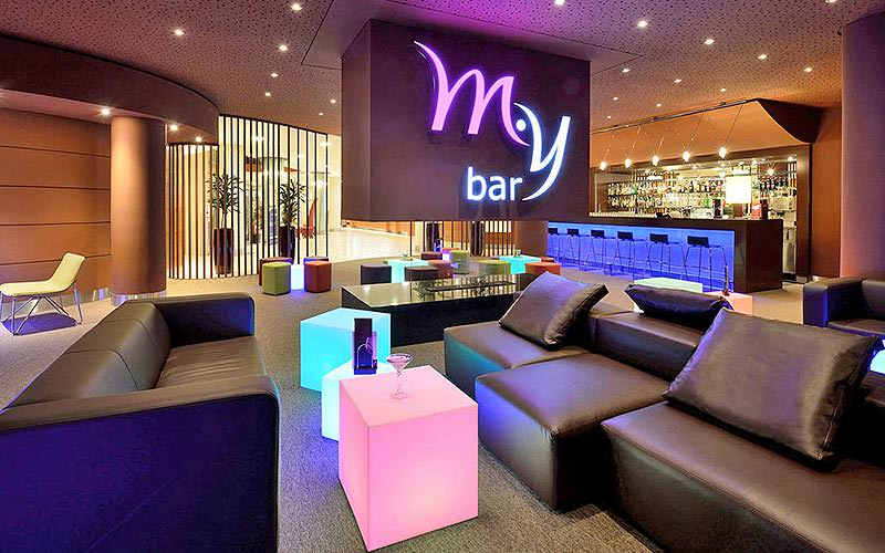 Leather seating and colourful tables in front of a wall with a lit-up My Bar sign, and a bar in the far background