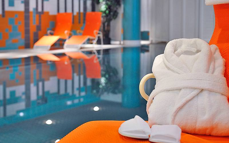 A white bathrobe on an orange sun lounger, with a blurred image of a pool in the background