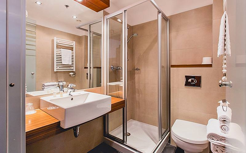A shower, toilet and sink in a wooden counter in a hotel bathroom