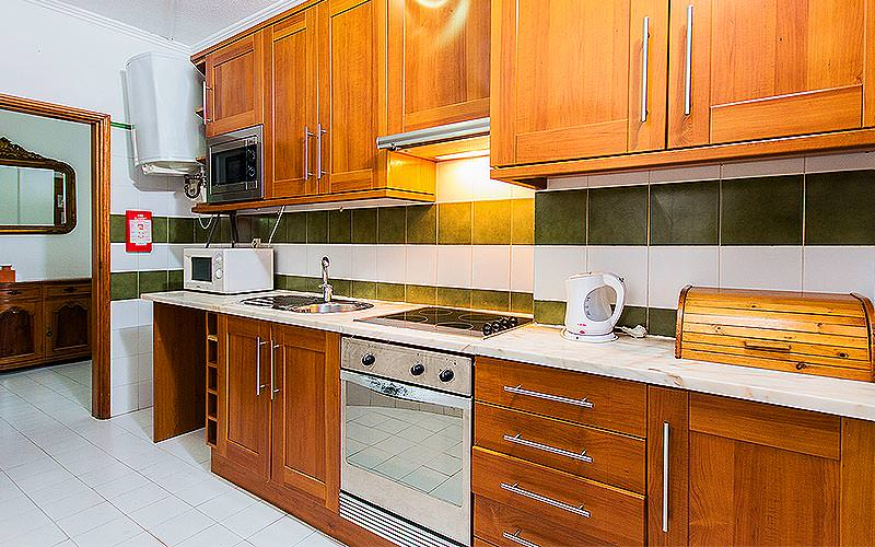 Wooden kitchen counters and oven, with appliances on the counters