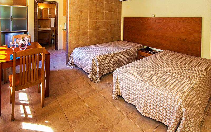 Two double beds with a bedside table in the middle and a table for two in the foreground