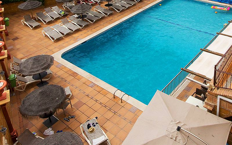 An outdoor pool surrounded by sun loungers
