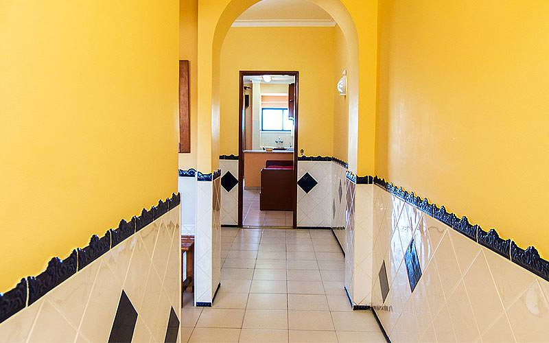 A yellow, white and blue tiled hallway with a sofa visible through an open door