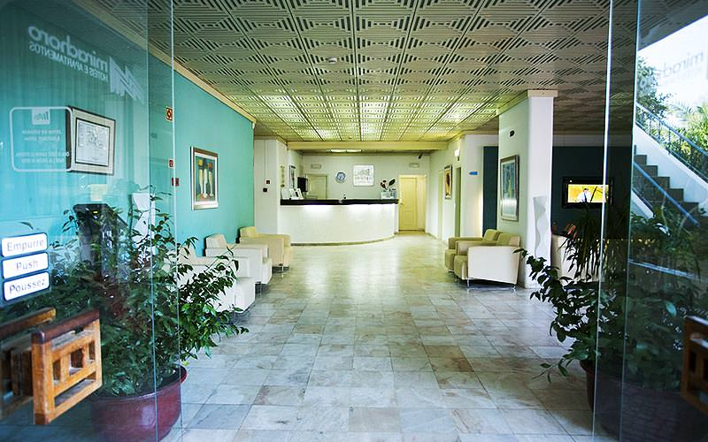 Blue reception with plants and white chairs along the walls, and a reception desk in the back