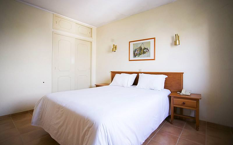 A white double bed in a plain hotel room, with wooden bedside tables on either side