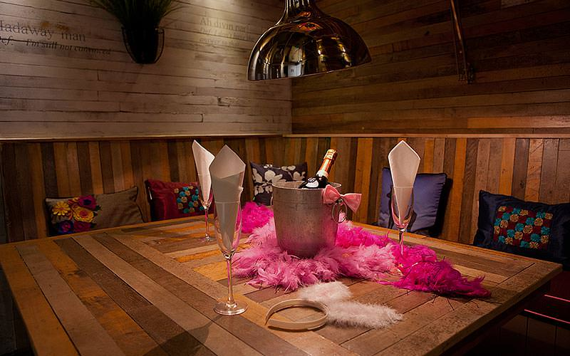 A wooden booth with colourful cushions on the seats, and a table in the middle topped with drinks and accessories