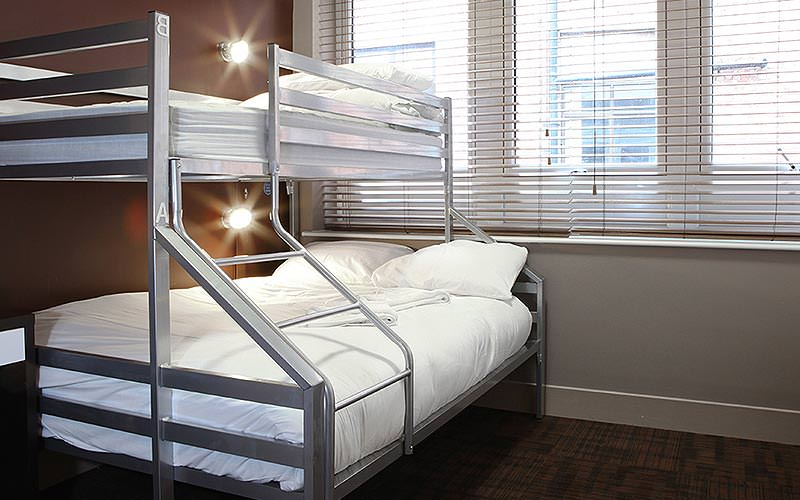 A silver bunk bed with white bedding