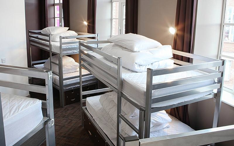 Three silver bunk beds in a hotel room