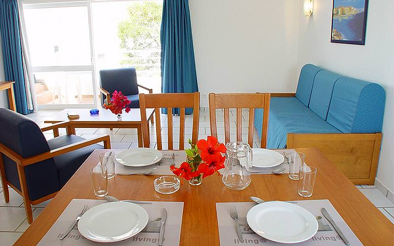 A dining table set for dinner with blue seating in the background