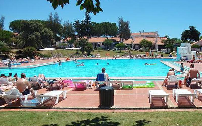 People sat on sun loungers, facing an outdoor pool