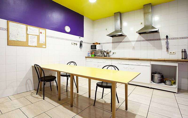 A table with three chairs in the middle of a kitchen, with kitchen counters in the background