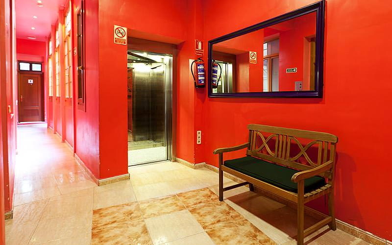 A red hallway with a bench and a mirror on the wall above in the foreground