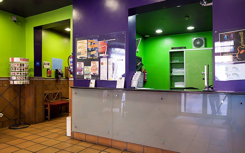 A reception desk in a purple wall, with a hallway in the background