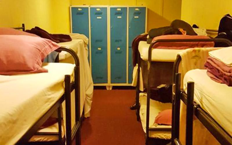 Bunk beds on either side of the wall with blue lockers in the background