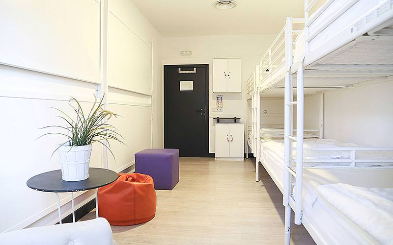 White bunk beds along one side of the wall, and purple and orange beanbags and a table on the other side