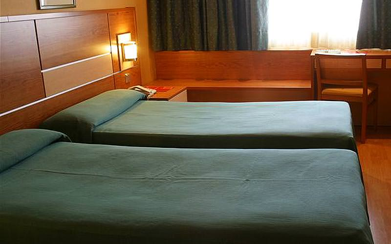 Two single beds topped with green bedding, with a desk and chair in the background