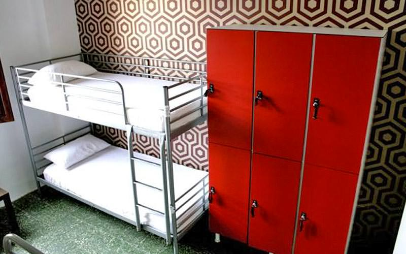 A bunk bed in a room with geometric wallpaper, and six red lockers by the beds