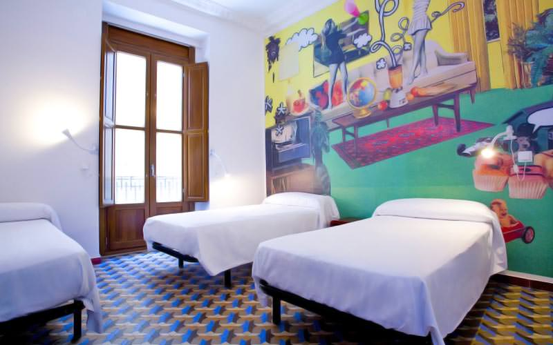 Three single beds in a room, with a colourful mural on the wall