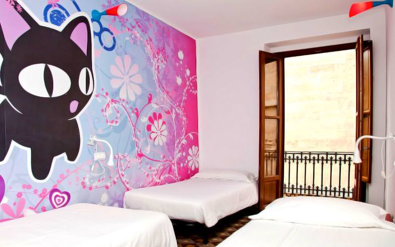 Three single beds in a room, with a pink mural on the wall with a cat