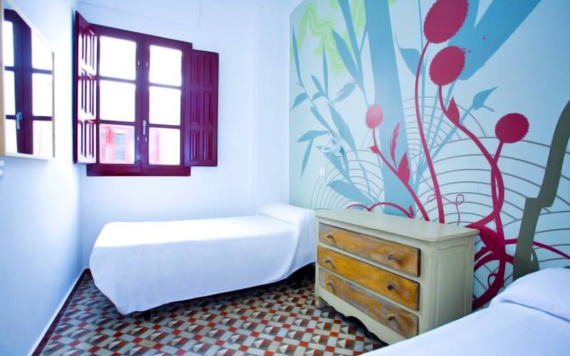Two single beds in a room, with a mosaic floor and a colourful design on the wall