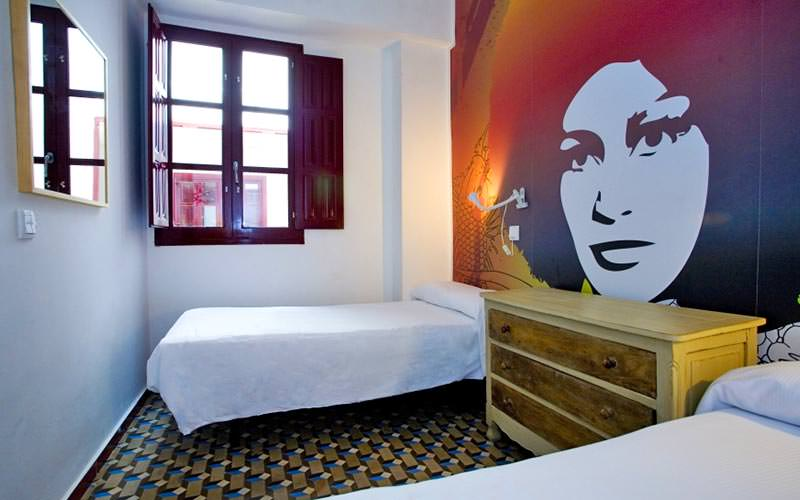 Two beds in a room with a woman's face on the wall