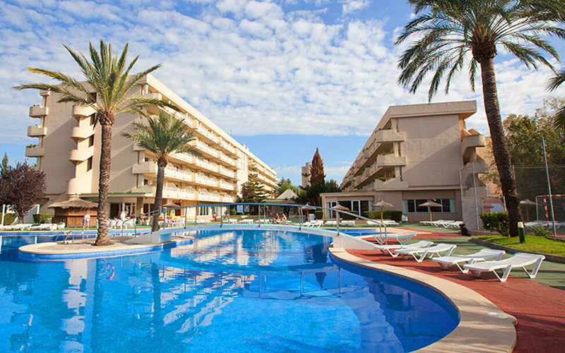 A L-shaped sofa bed facing a TV and French doors, with a table topped with fruit and wine in the foreground