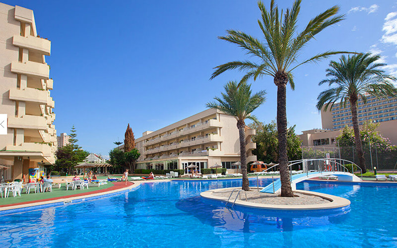 Circular tables and chairs in front of a bar, lined with bar stools