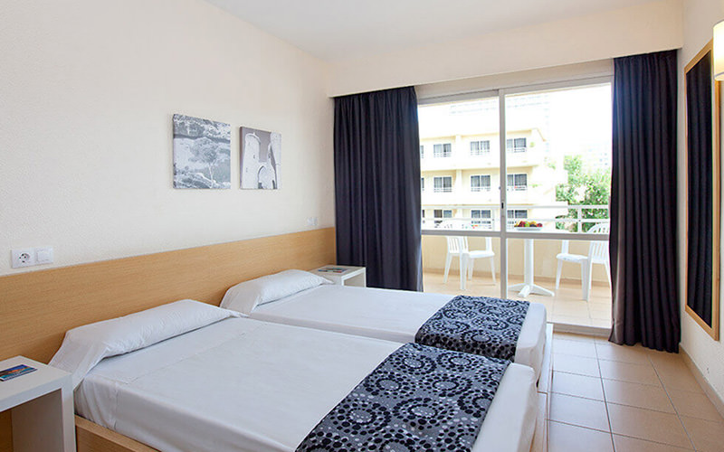 Glass doors with plants and two brown chairs on each side