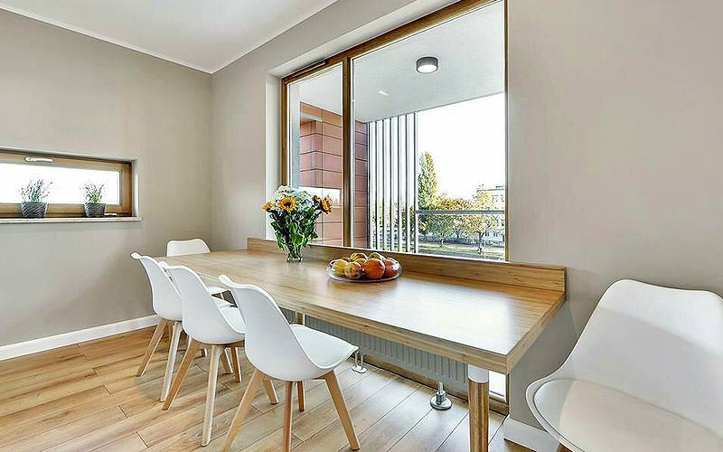 A dining table next to a large window in a Sun and Snow Apartments apartment