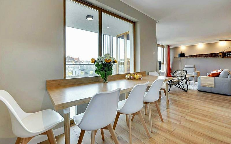 A dining table with lounge area in the background at Sun and Snow Apartments