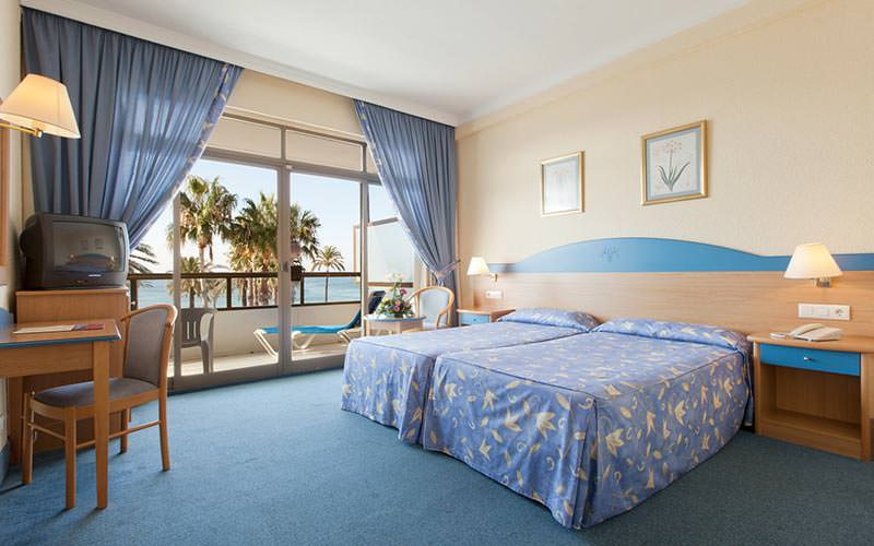 Two blue single beds in a hotel room, facing a desk, TV and chair, with French doors leading to a balcony in the back