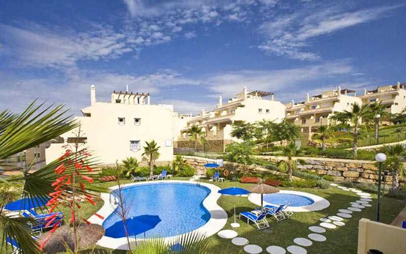 Outdoor pools and gardens, as well as the white building exterior of the Colina Del Paraiso Apartments, during the day