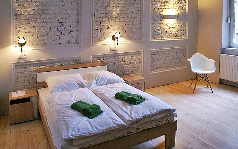 A double bed in a room with painted white bricks behind the bed