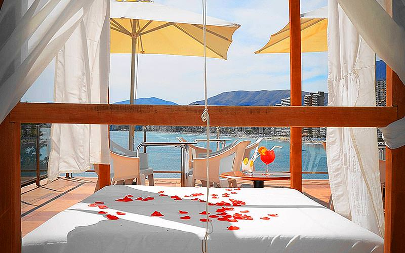 An outdoor bed with rose petals sprinkled on and the backdrop of mountains and the sea