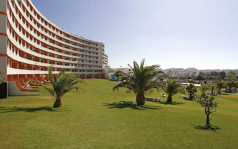 Green gardens featuring small trees, with the Paraiso Albufeira Hotel exterior in the background