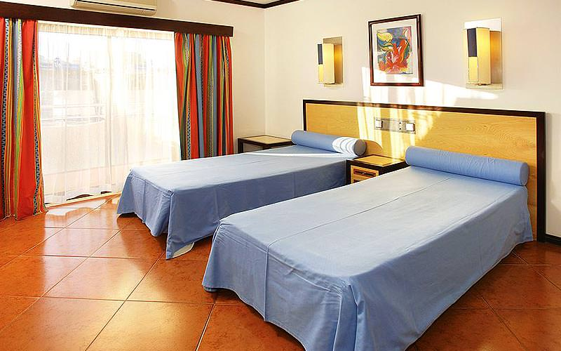Two blue single beds in a hotel room
