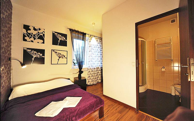 A spacious double bedroom with pictures of flowers on the wall and the bathroom door open