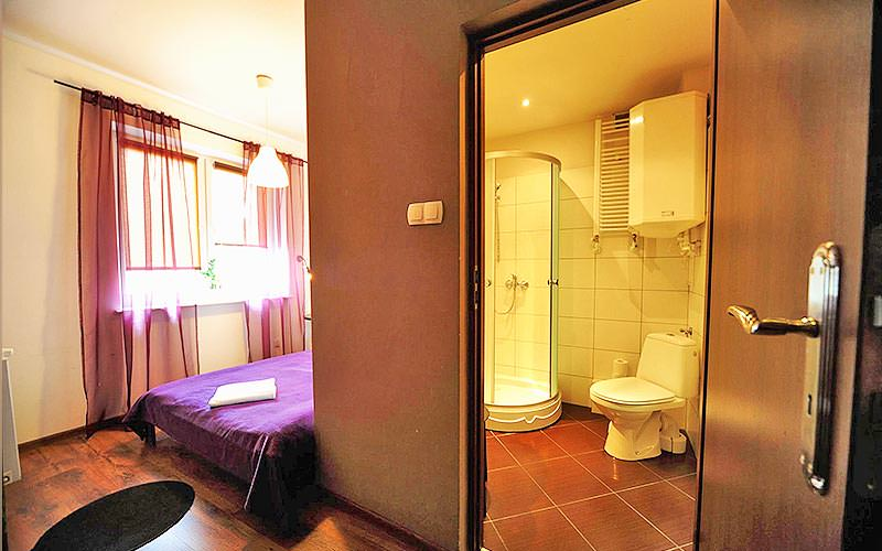 A bathroom door open with the end of the bed showing from behind the wall