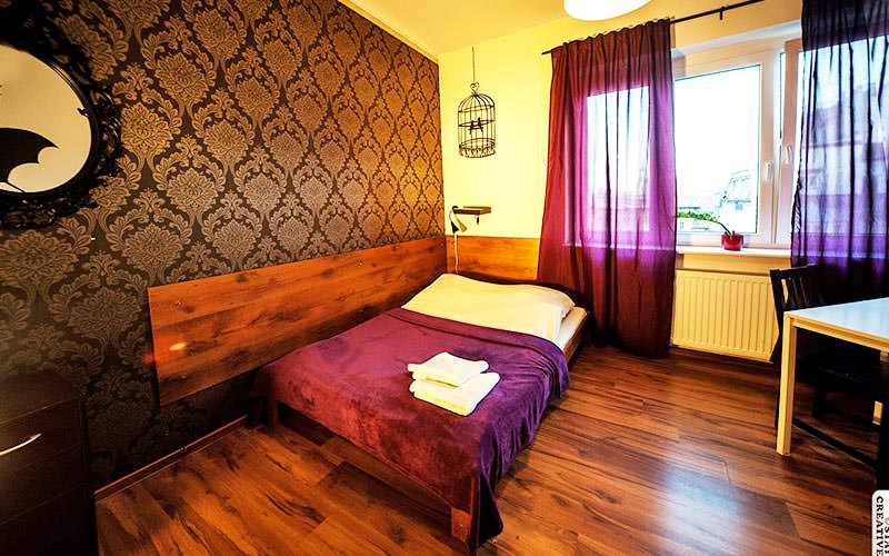 A double bed in a room with paisley print wallpaper and purple curtains
