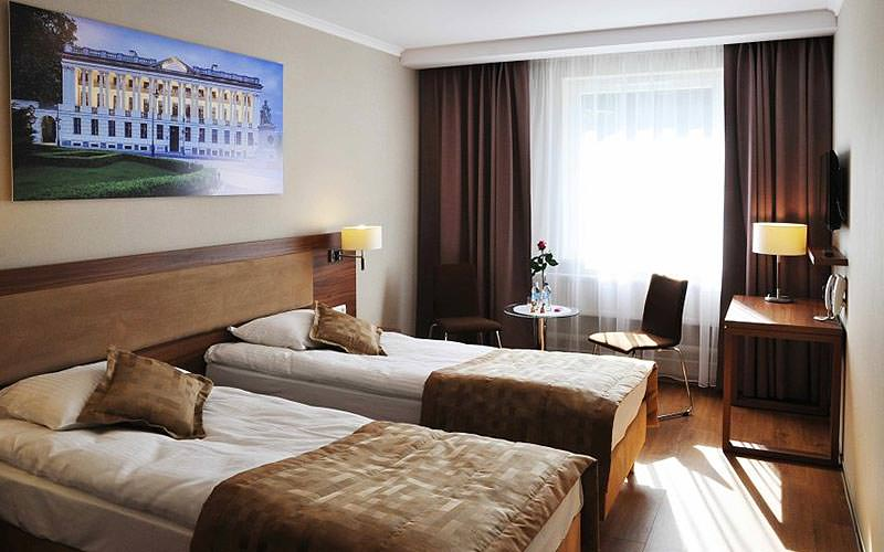 Two single beds in a room with a canvas of a huge, white building displayed behind the bed