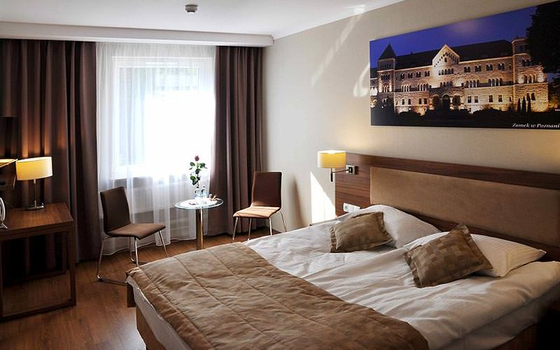 A large double bed in a brown colour themed room, with a photograph of a building mounted on the wall