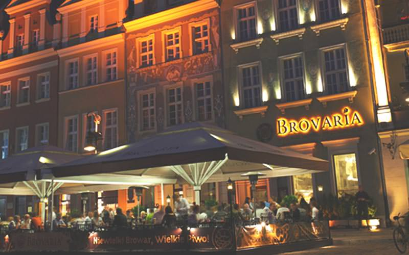 The exterior of Hotel Brovaria with outdoor seating under massive umbrellas