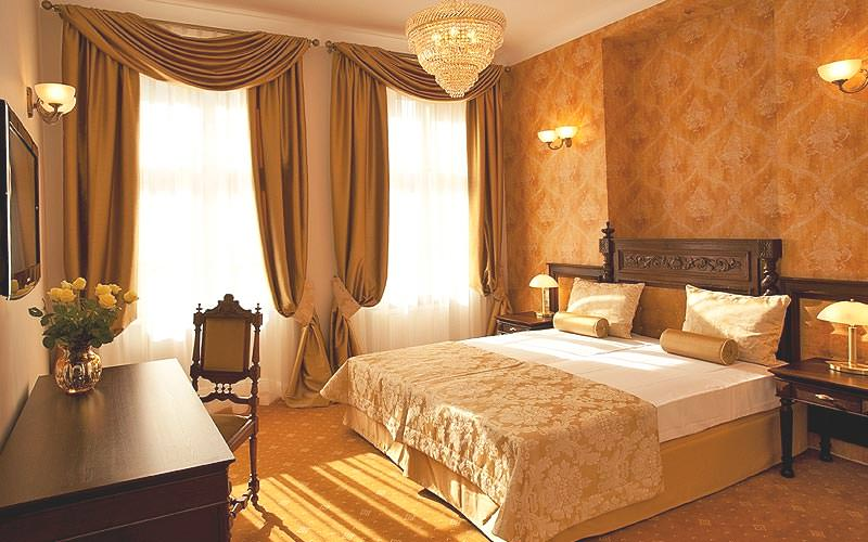 A plush bedroom with drape curtains and lavish decor