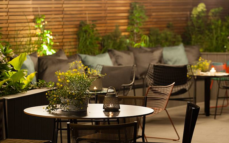 An outdoor seating area with plants and cushions