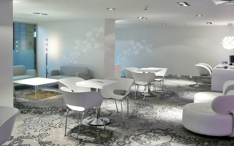 A seating area with white seats, tables and walls