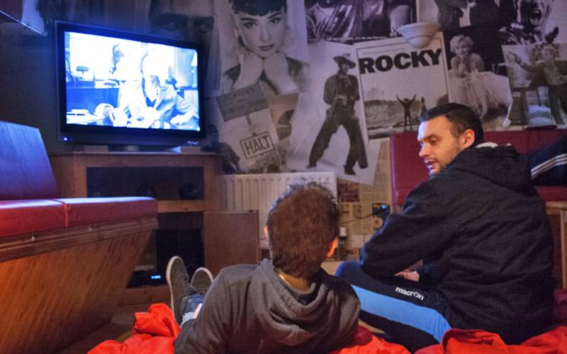 Two men sitting on the floor and watching a TV