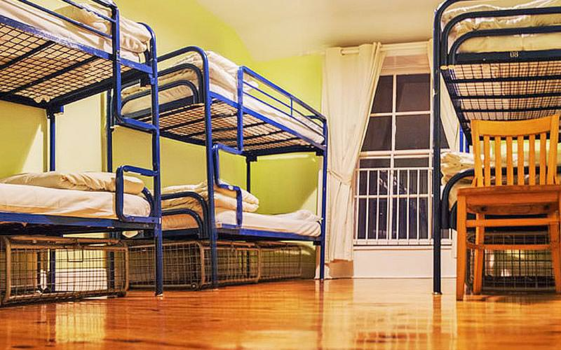 A room containing multiple blue metal framed bunk beds
