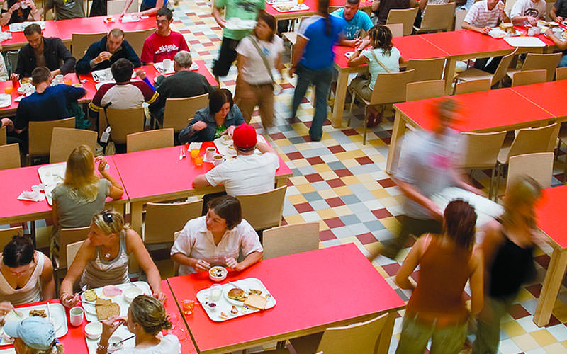 A packed canteen style diner with red table tops